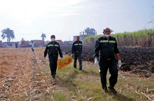Rescue workers prepare to remove a body from the scene of a balloon crash outside al-Dhabaa village, just west of the city of Luxor, 510 kilometers (320 miles) south of Cairo, Egypt, Tuesday, Feb. 26, 2013. A hot air balloon flying over Egypt's ancient city of Luxor caught fire and crashed into a sugar cane field on Tuesday, killing at least 18 foreign tourists, a security official said. The casualties included French, British, Belgian, Hungarian, Japanese nationals and nine tourists from Hong Kong, Luxor Governor, Saad told reporters. (AP Photo/Hagag Salama) Photo: Hagag Salama