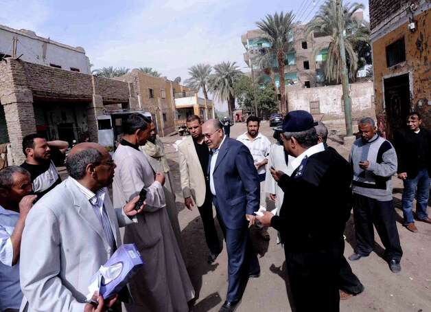 Luxor Governor Ezzat Saad, center, speaks to reporters in al-Dhabaa village, just west of the city of Luxor, 510 kilometers (320 miles) south of Cairo, Egypt, Tuesday, Feb. 26, 2013. A hot air balloon flying over Egypt's ancient city of Luxor caught fire and crashed into a sugar cane field on Tuesday, killing at least 18 foreign tourists, a security official said. The casualties included French, British, Belgian, Hungarian, Japanese nationals and nine tourists from Hong Kong, Luxor Governor, Saad told reporters. (AP Photo/Ibrahim Zayed) Photo: Ibrahim Zayed