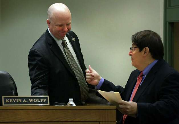 After saying he'd vote for the appeal, Commissioner Kevin Wolff gets the thumbs-up from George Hernandez Jr., president and CEO of University Health System. Photo: Photos By Bob Owen / San Antonio Express-News