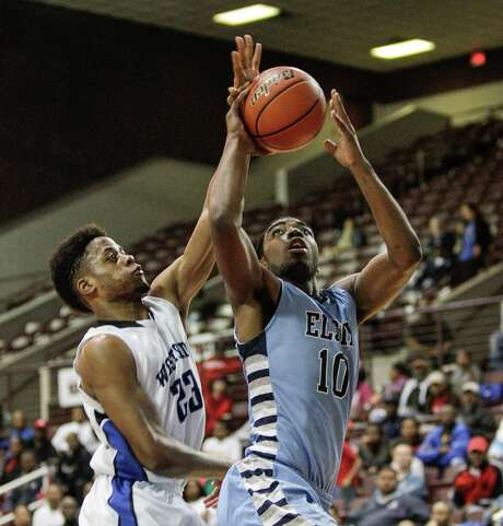 Westside forward Franklin Iheanacho, left, blocks a shot by Elsik's Caleb Bedford during Tuesday night's game at the Campbell Center. Photo: Bob Levey, Photographer / ©2013 Bob Levey