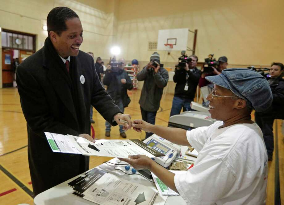 Chicago Alderman Anthony Beale, a Democrat, speaks with election judge Nancy Karen as he casts his vote in Chicago, Tuesday, Feb. 26, 2013, in the special primary election to replace former U.S. Rep. Jesse Jackson in Illinois' 2nd Congressional District. Beale is one of three front-runners in the primary. The others include former state Rep. Robin Kelly and former U.S. Rep. Debbie Halvorson. They were among 14 Democrats and four Republicans in the special primary, but the Democratic winner is expected to sail through the April 9 general election because of the heavily Democratic region. (AP Photo/M. Spencer Green) Photo: M. Spencer Green