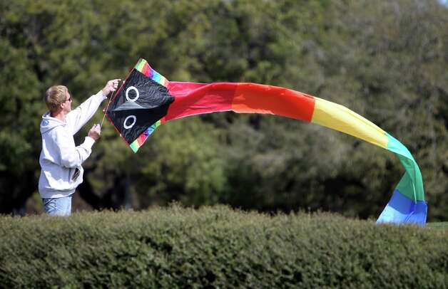 Bill Kopitzke raises his kite towards the sky in hopes a gust of wind will launch into the air at Hermann Memorial Park on Tuesday, Feb. 26, 2013, in Houston. Winds will decrease today, and sunny pleasant weather expected tomorrow. Photo: Mayra Beltran, Houston Chronicle / © 2013 Houston Chronicle