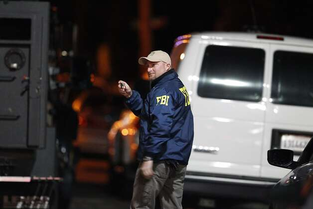 An FBI investigator gestures back from N. Branciforte Avenue in Santa Cruz, Calif., on Tuesday night, February 26, 2013, after an officer involved shooting left two Santa Cruz police officers and a suspect dead near the intersection of Doyle Street and N. Branciforte Ave. Photo: Carlos Avila Gonzalez, The Chronicle