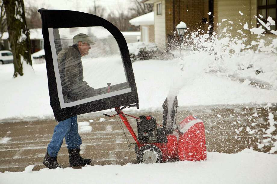 Lloyd Anderson, 88, uses a snow blower with a canopy to clear his driveway on Lover's Lane in St. Joseph, Mo. on Tuesday, Feb. 26, 2013. A major winter storm paralyzed parts of the nation's midsection Tuesday, dumping a fresh layer of heavy, wet snow atop cities still choked with piles from the previous system and making travel perilous from the Oklahoma panhandle to the Great Lakes. Photo: Sait Serkan Gurbuz, Associated Press / St. Joseph News-Press