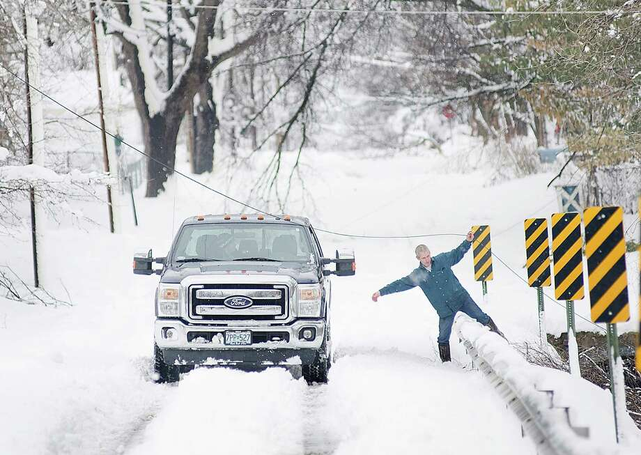 Tedd Hendrix, of Sedalia, Mo., frees a line of cable from downed branches Tuesday, Feb. 26, 2013, as he works to tie the line off so that it is elevated and out of the road. A snow storm, the second in less than a week, dumped about a foot of snow in Sedalia, knocking out power around the town and collapsing the roofs of several buildings. Photo: Sydney Brink, Associated Press / Sedalia Democrat