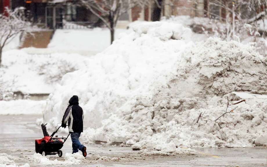 A man pushes a snowblower around a giant pile of snow left by road crews in the Country Club Plaza shopping district of Kansas City, Mo., Tuesday, Feb. 26, 2013. Photo: Orlin Wagner, Associated Press / AP