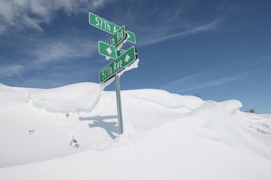 Drifted snow nearly buries a street sign in rural Pratt County, Kan. on Tuesday, Feb. 26, 2013.  Feb