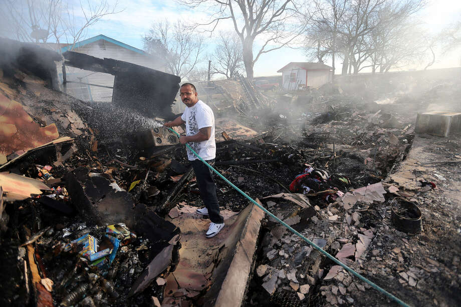 Juan Lugo puts out a hot spot at his uncle's three-unit apartment building in the 8100 block of Pearsall Road, one of the buildings burned in a fire the day before that took the lives of a woman and her two young sons who lived in a nearby home. Photo: Photos By Jerry Lara / San Antonio Express-News