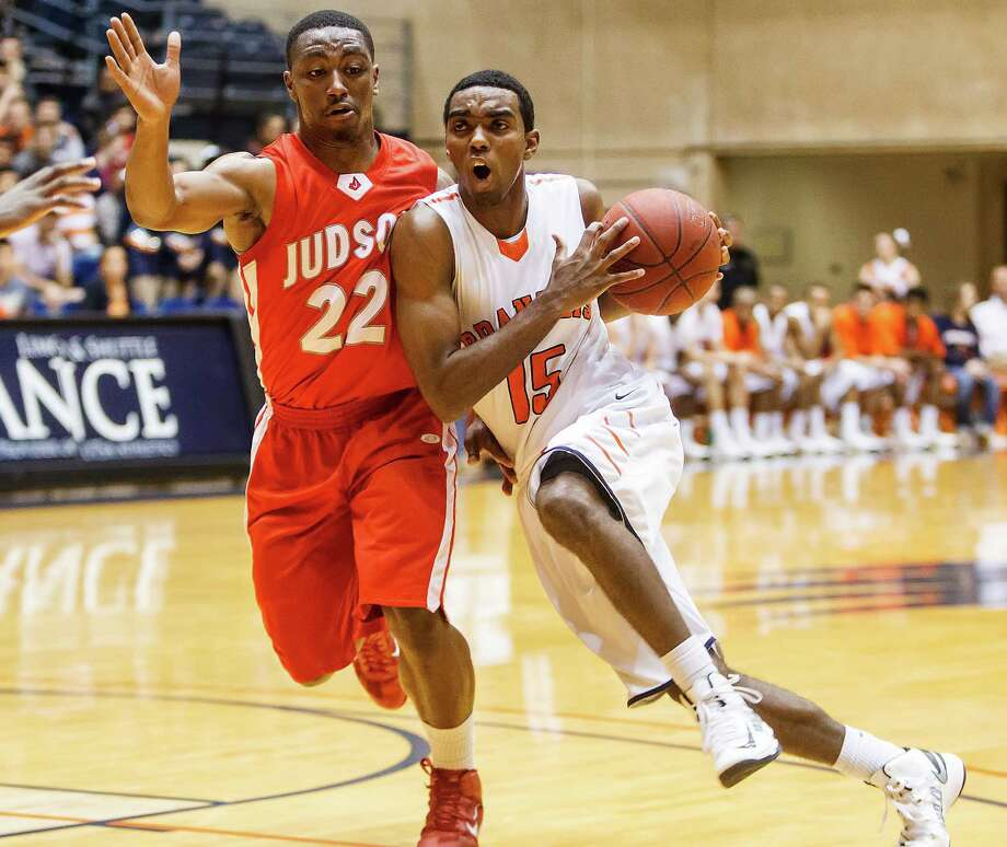Brandeis' Justin Graham (right) tries to drive past Judson's Jarveon Williams during the second quarter at the Convocation Center. The Broncos won 60-53. Photo: Marvin Pfeiffer / San Antonio Express-News