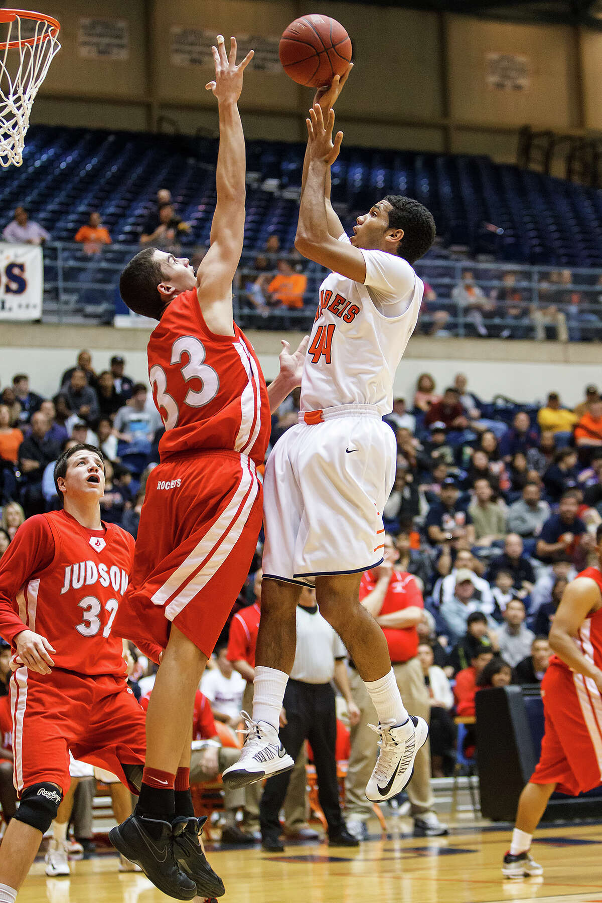 Brandeis' Jonathan Robinson (right) tries to get a shot over Judson's David Wacker during the first half of their Class 5A boys basketball third round game at the UTSA Convocation Center on Tuesday, Feb. 26, 2013. Brandeis won the game 60-53.