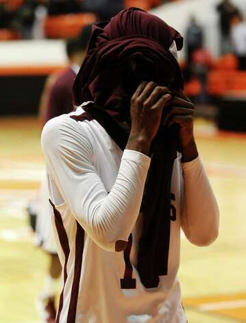 Silsbee High School player Chris Elam, #10, covers his face with his jersey after a loss in the Class 3A Region III quarterfinals game against Houston Yates High School 100 - 85.   Photo taken: Randy Edwards/The Enterprise Photo: Randy Edwards