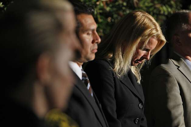 Santa Cruz Mayor Hilary Bryant bows her head as Police Chief Kevin Vogel identifies  the two detectives who were killed in the line of duty. Photo: Carlos Avila Gonzalez, The Chronicle