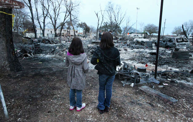 Siblings Brooke (left) and Bethany Zepeda pause to view the devastation of a fire that took the lives of their aunt and cousins on Tuesday, Feb. 26, 2013. The two sisters were there for a candlelight vigil joined by several hundred other mourners for Roxanne Ordonez and her one-year-old twin boys, Daniel and Orlin, who perished from the fire fueled by high winds on Monday afternoon. Photo: Kin Man Hui, San Antonio Express-News / © 2012 San Antonio Express-News