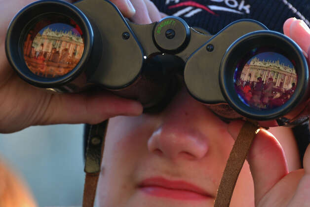 Faithful looks at ST Peter's basilica through binoculars on St Peter's square ahead of Pope Benedict XVI last weekly audience on February 27, 2013 at the Vatican. Pope Benedict XVI will hold the last audience of his pontificate in St Peter's Square on Wednesday on the eve of his historic resignation as leader of the world's 1.2 billion Catholics.  AFP PHOTO / GABRIEL BOUYS Photo: AFP, AFP/Getty Images / 2013 AFP
