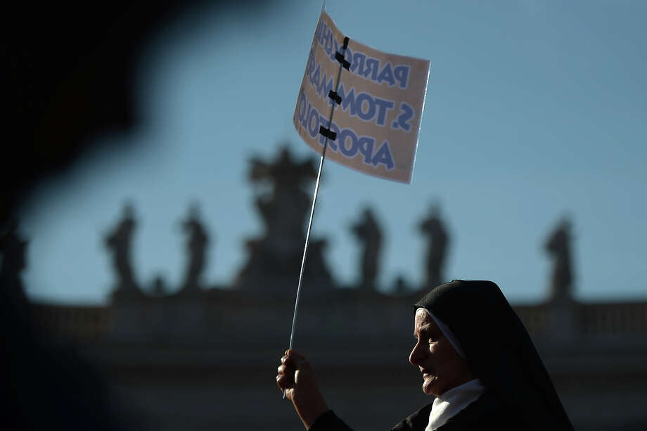 A nun holds a placard on St Peter's square ahead of Pope Benedict XVI last weekly audience on February 27, 2013 at the Vatican. Pope Benedict XVI will hold the last audience of his pontificate in St Peter's Square on Wednesday on the eve of his historic resignation as leader of the world's 1.2 billion Catholics.    AFP PHOTO / FILIPPO MONTEFORTE Photo: AFP, AFP/Getty Images / 2013 AFP