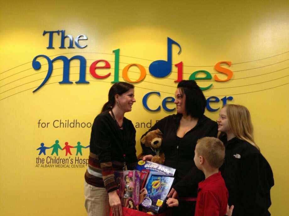 Dylan Romanowski, 7, donates toys to Albany Medical Center's Angie Silipigno, left, child life specialist at the Melodies Center on Wednesday, Feb. 27, 2013. With Dylan are his mother, Karrie Romanowski, and sister Makayla Romanowski. (Skip Dickstein/Times Union)