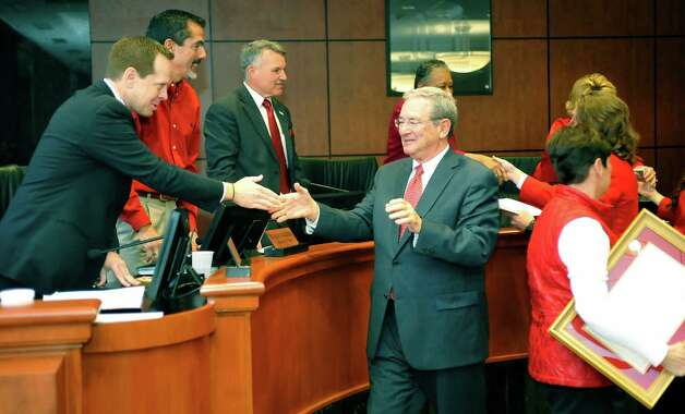 Lamar President Jimmy Simmons, center, shakes hands with Beaumont City Manager Kyle Hayes, left, and others after he and his wife Susan, right,  received the Proclamation which Susan is carrying.    On Tuesday, February 26, 2013, the Beaumont City Council, during their regular meeting, voted unanimously on an ordinance renaming a street after Lamar University President Jimmy Simmons. A portion of University Drive, that is between E. Cardinal Drive and E. Lavaca Street, will be renamed Jimmy Simmons Boulevard.   Council also gave him and his wife Susan a Proclamation. Dave Ryan/The Enterprise Photo: Dave Ryan