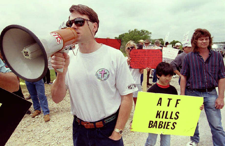 Kerry Kinchen uses a bullhorn to lead protesters in an anti-ATF demonstration at the checkpoint leading to the remains of the Branch Davidian cult compound 24 April 1993. The 51-day standoff, which began 28 February in a shootout with Alcohol Tobacco and Firearms agents ended 19 April when the cult's compound burned to the ground, with an estimated 86 members of the cult still inside. Photo: DAVID AKE, AFP/Getty Images / AFP
