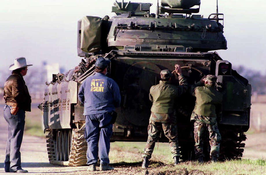 Agents from the Bureau of Alcohol, Tobacco and Firearms (ATF) secure the door of a Bradley armored personel carrier 4 March 1993 near the Mt. Carmel compound of the Branch Davidian religious sect, Texas.  The sect is in the fifth day of an armed standoff against ATF and FBI agent. Photo: BOB PEARSON, AFP/Getty Images / 2012 AFP