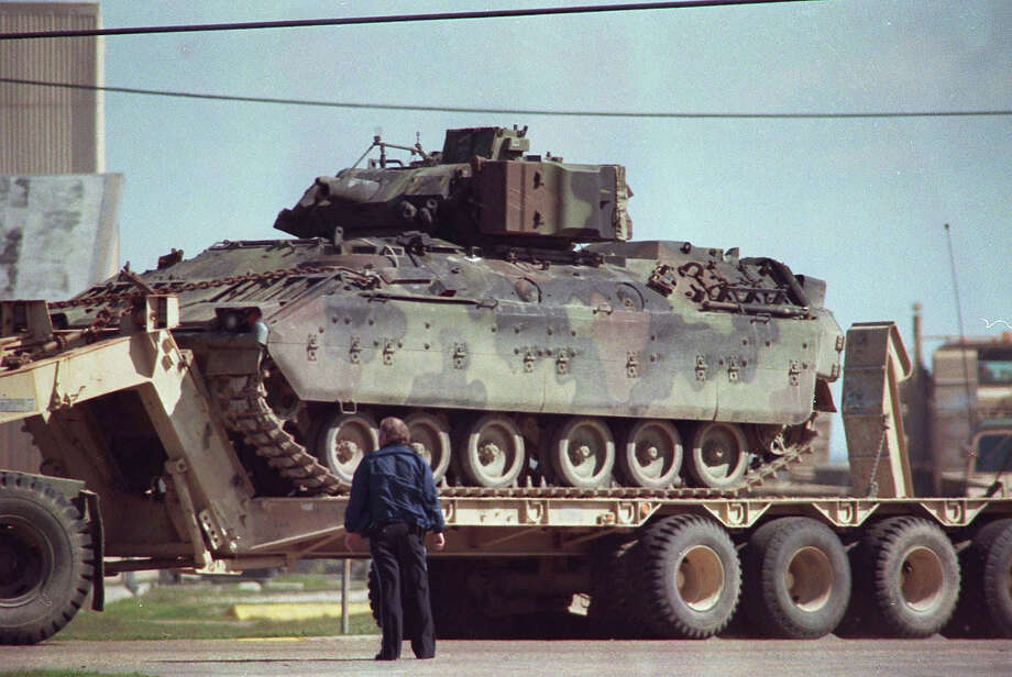 A law enforcement official watches as an armored personnel carrier is deployed from the command center at the Texas State Technical College campus in Waco, Texas in this March 1993  photo. Investigators with the General Accounting Office want to determine whether federal agents improperly used military equipment during the 1993 Branch Davidian standoff, the Waco Tribune-Herald reported Sunday, Dec.7,1997.  (AP Photo) Photo: ASSOCIATED PRESS / AP1993