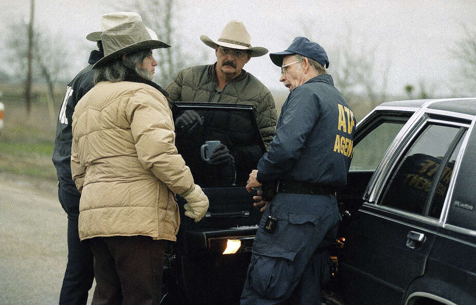 Federal and local law enforcement officials confer at a roadblock near the Mount Carmel compound of