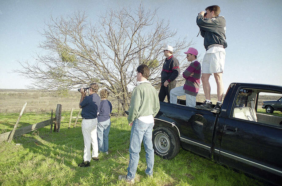 Baylor University students and a couple on vacations from Mississippi try to catch sight of the Branch Davidians' compound near Waco, Texas on Thursday, March 5, 1993. A steady stream of rubberneckers stop at the hilltop perch more than five miles from the site of the standoff. Photo: Pat Sullivan, AP / AP