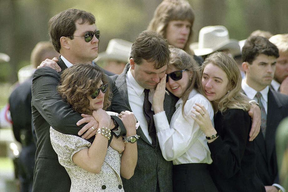 Mourners at the funeral of Alcohol, Tobacco and Firearms agent Steve Willis comfort each other at Willis' grave in Houston on Friday, March 5, 1993. The mourners are members of the Texas Spokes Sports Car Club of Austin, Texas, of which Willis was a member. At left are Tom and Heather Holt, and far right is Tani Barr. The couple in the middle is unidentified. (AP Photo/Tim Johnson) Photo: Tim Johnson, ASSOCIATED PRESS / AP1993
