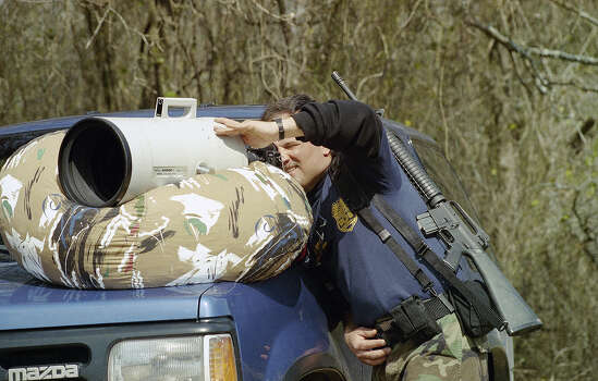 An agent with the Bureau of Alcohol, Tobacco and Firearms takes a peek through a special 2,000-mm lens used by a news photographer covering the standoff of the Branch Davidian cult near Waco, Texas on Saturday, March 6, 1993. The lens is propped on a beanbag chair for stability. Photo: Rick Bowmer, AP / AP
