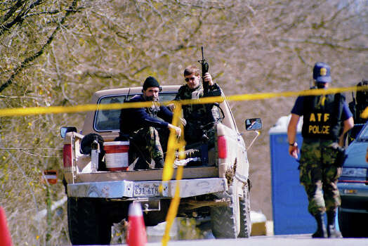 Agents of the Bureau of Alcohol, Tobacco and Firearms ride in the back of a farmer's pickup truck as he drives to work his fields in Waco, Texas Mar. 9, 1993. Local farmers must be escorted by agents when they work near the Branch Davidian compound outside of Waco, Texas. Photo: Richard Bowmer, AP / 1993 AP