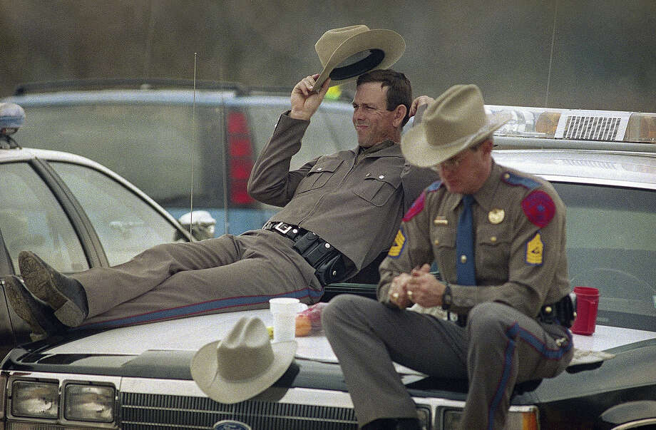 Two Texas Department of Public Safety officers take it easy at a checkpoint near the Branch Davidian compound on Friday, March 20, 1993. Law officers have been in a standoff with David Koresh and his Branch Davidian followers since February 28 gunfights that ended with four Alcohol, Tobacco and Firearms agents and at least two cultists dead. Photo: Ron Heflin, AP / AP