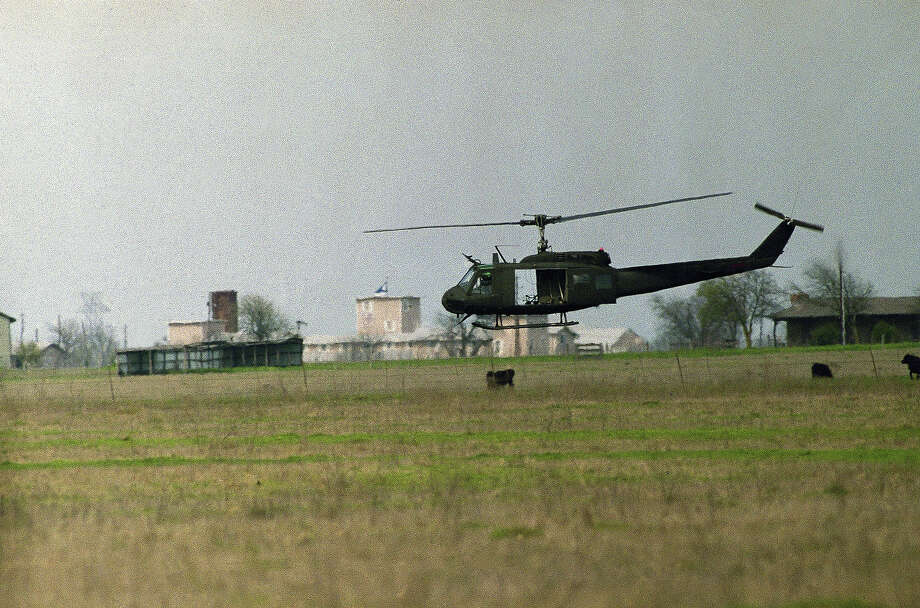 A helicopter hovers near the Branch Davidian compound (background) in Waco, Texas on Tuesday, March 23, 1993 as cult extremists continue their standoff with justice officials. Members of the cult have been slowly trickling out of the armed compound which has been under siege for 24 days. Photo: David Phillip, AP / AP