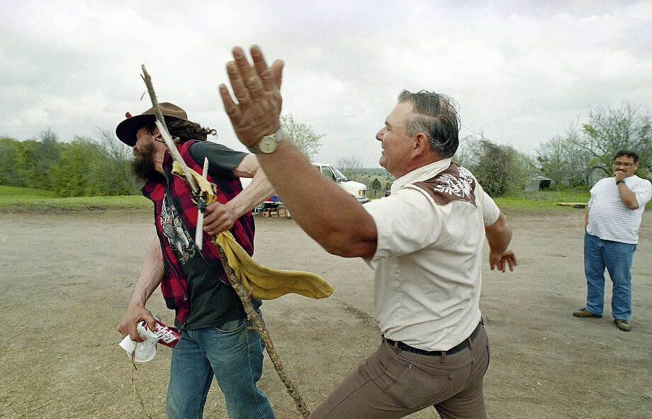 Billy Walker backhands an unidentified man who cursed him for selling T-shirts near the Waco, Texas, compound of the Branch Davidians on Monday, March 30, 1993. A number of vendors have gathered near the site to sell goods to spectators who gather for a view of the compound which has been under siege by federal authorities for a month. Photo: Dave Martin, AP / AP