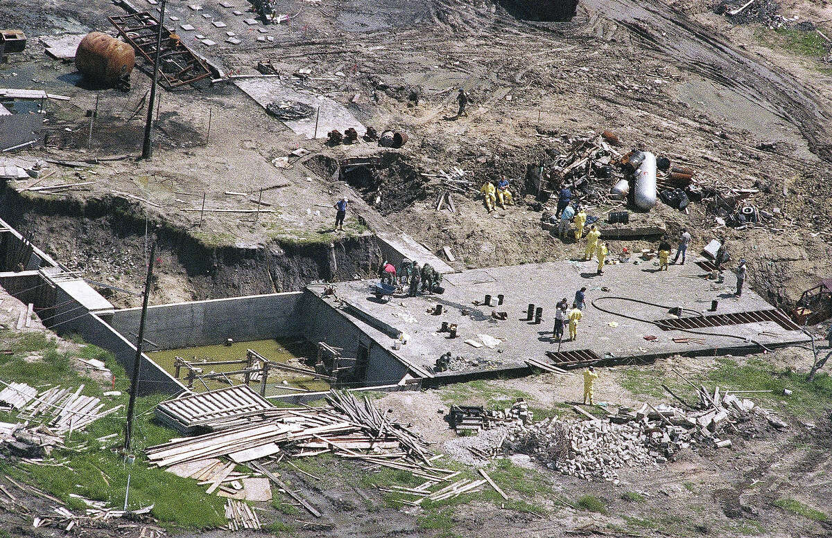 Investigators work on top of the underground bunker at the Branch Davidian compound near Waco, Texas on Monday, May 3, 1993 as the search continues for more bodies at the burned out compound. The heavily armed religious sect's complex burned on April 19, killing an estimated 72 people.
