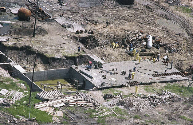 Investigators work on top of the underground bunker at the Branch Davidian compound near Waco, Texas on Monday, May 3, 1993 as the search continues for more bodies at the burned out compound. The heavily armed religious sect's complex burned on April 19, killing an estimated 72 people. Photo: Ron Heflin, AP / AP