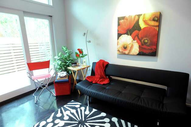 In the spare bedroom, a black futon and a painting of red and orange poppies dominate. Feb. 20, 2013. Photo: Billy Calzada, San Antonio Express-News / San Antonio Express-News
