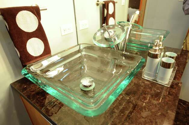 Two clear glass sinks have unusual spouts that pour water onto a glass disc before it falls into the bowl. Feb. 20, 2013. Photo: Billy Calzada, San Antonio Express-News / San Antonio Express-News