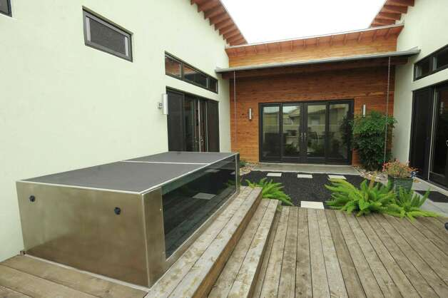 The patio has different textures, including stone, slate, cedar decking and recycled crushed rubber in various places. A stainless steel plunge pool dominates one end of the patio. Feb. 20, 2013. Photo: Billy Calzada, San Antonio Express-News / San Antonio Express-News