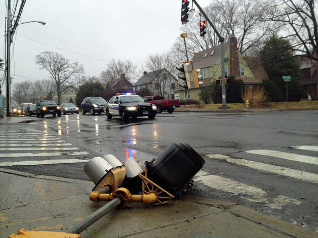 Heavy winds this morning brought one traffic signal crashing to the ground and left another signal dangling four feet above he roadway at the intersection of Courtland Avenue and Glenbrook Road. The intersection remained open with a police car stationed in the roadway. Photo: John Nickerson