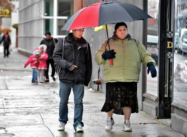 Andres Baraja and his mother, Angelica Morales, share an umbrella as they run errands in Troy Wednesday Feb. 27, 2013.  (John Carl D'Annibale / Times Union) Photo: John Carl D'Annibale / 00021330A
