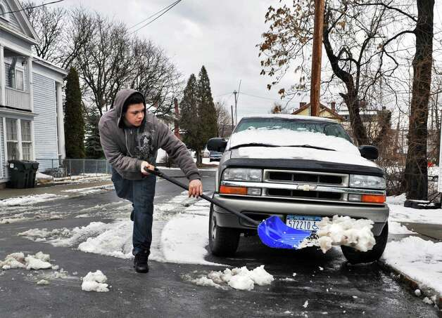 Shawn Guilbault, 17, shovels snow and slush from in front of his Schuyler Street home in Cohoes Wednesday Feb. 27, 2013.  (John Carl D'Annibale / Times Union) Photo: John Carl D'Annibale / 00021330A