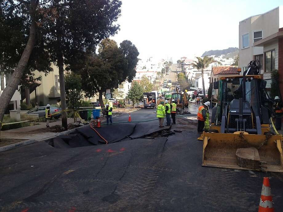 A sinkhole where a 16-inch water main broke on 15th Avenue near Wawona Street in San Francisco on Feb. 27, 2013, damaging 23 homes and 12 cars. Photo: Will Kane, San Francisco Chronicle