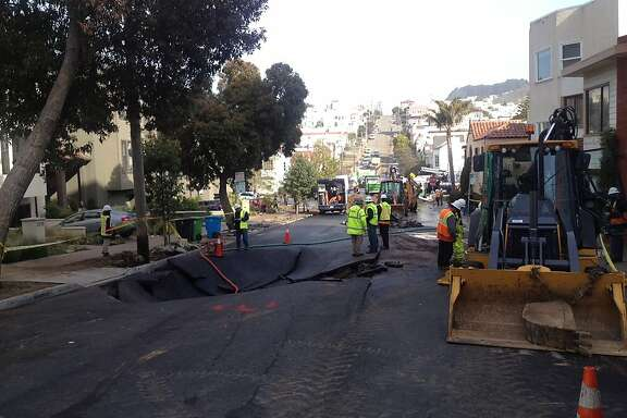 A sinkhole where a 16-inch water main broke on 15th Avenue near Wawona Street in San Francisco on Feb. 27, 2013, damaging 23 homes and 12 cars.