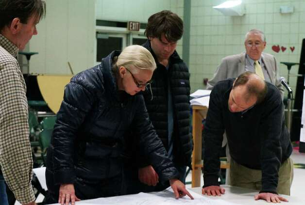 Residents look at a map for a proposed 2-lot subdivision on the Elks Club property during a public hearing Tuesday while the club's attorney, Peter Gelderman, looks on. Photo: Genevieve Reilly / Fairfield Citizen