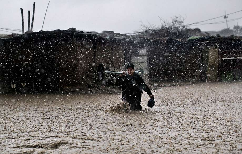 Appliances saved: Amid a downpour, an Afghan refugee wades through high water with a fan and a lamp he rescued from a flooded shanty on the outskirts of Islamabad, Pakistan. Photo: Muhammed Muheisen, Associated Press