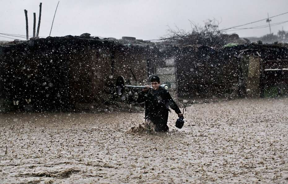 Appliances saved: Amid a downpour, an Afghan refugee wades through high water with a fan and