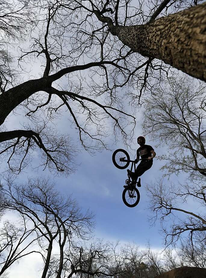 A bicyclist flies through the trees as he jumps a dirt mound at a bike park in Austin, Texas. Photo: Eric Gay, Associated Press