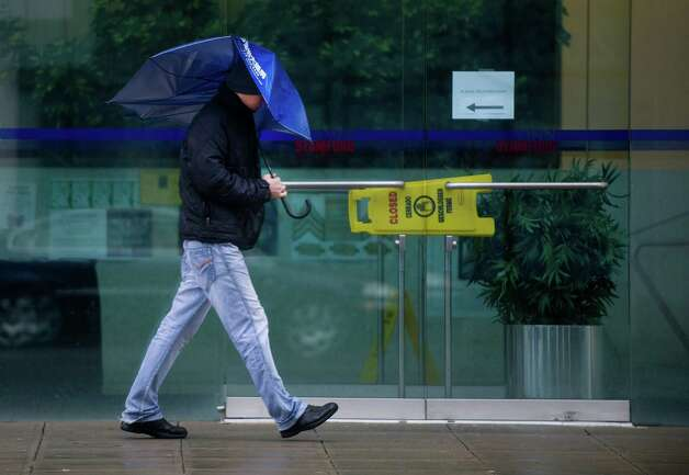 A pedestrian uses a broken umbrella to shield his face from wind and rain on Broad Street in Stamford, Conn., on Wednesday, February 27, 2013. Photo: Lindsay Perry / Stamford Advocate