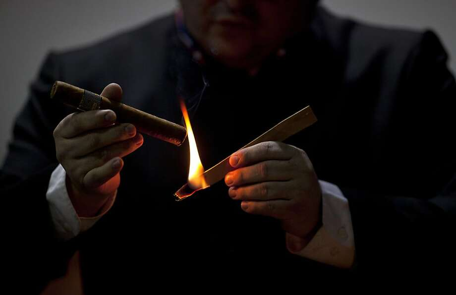 A man lights a cigar during the inauguration of the 15th Cigar Festival in Havana, Cuba, Tuesday, Feb. 26, 2013. Cigar enthusiasts from around the world come to Cuba during the annual celebration to visit tobacco farms and factories and savor new cigar brands. Photo: Ramon Espinosa, Associated Press