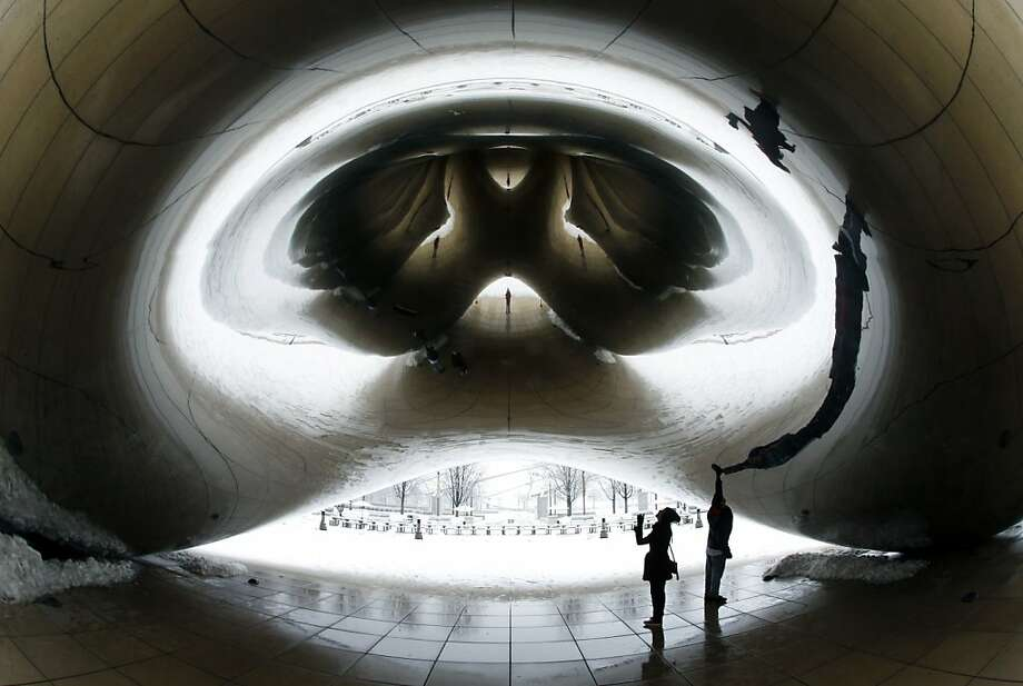 "Visitors investigate the underbelly of Anish Kapoor's stainless-steel ""Cloud Gate"" as snow blankets the outside of the sculpture in Chicago's Millennium Park. Photo: Charles Rex Arbogast, Associated Press"