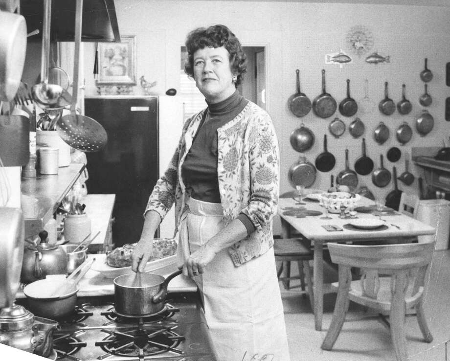 "FILE -- Julia Child in her kitchen, surrounded by an assortment of cooking utensils from around the world and a dining table from Norway, in Boston, March 5, 1964. Child was born 100 years ago Aug. 15, 2012, and without her, the phrase ""aspiring food writer"" might never have been uttered in the United States. (Bill Aller/The New York Times) Photo: BILL ALER / NYTNS"